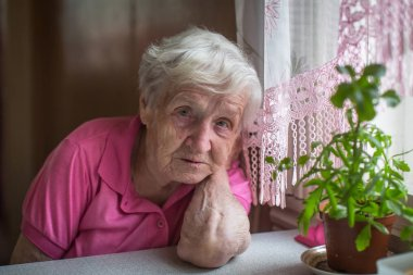Portrait of unhappy older woman sitting at the table.