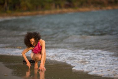 Multicultural asian woman kneel on the surf line on the sea beach.