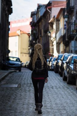 Treveller woman walks through the narrow pavement streets. Porto, Portugal.
