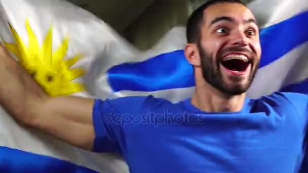Uruguaiano ventilatore che tiene la bandiera nazionale