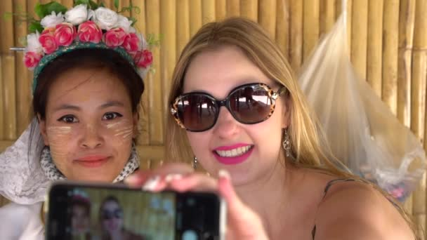 Tourist taking selfie photos with a Long Neck woman in traditional costume