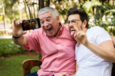 Dad and son taking selfie and having fun in the park