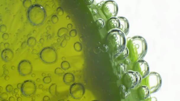 Sparkling bubbles water with a slice of lime. Slow motion macro footage.