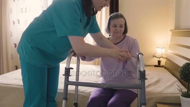 Gondozó-segítő vezető nő felkelni, és sétára a walker