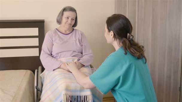 Donna anziana su sedia a rotelle in casa di riposo con la sua assistente di cura