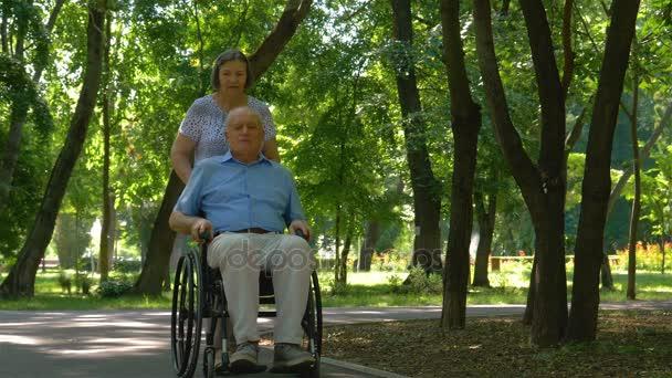 Starší žena tlačí manžela na invalidním vozíku venku