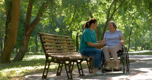 Badante ne alla disattivato donna maggiore in sedia a rotelle allaperto