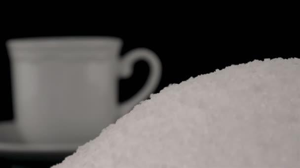 Lžíci bílého cukru v šálku kávy na černém pozadí