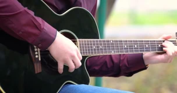 Mladý muž ruce hraje akustická kytara artist hudebník venku