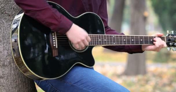 Detail osoby rukou hraje akustická kytara artist hudebník venku.