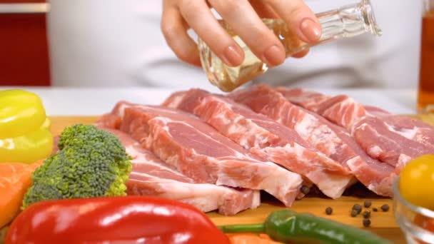 Žena ruce přilévat olej čerstvé syrové maso k vaření se zeleninou. Dolly zpomalený záběr.