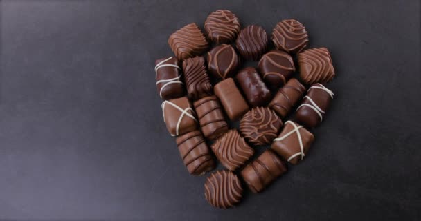 Čokoládové pralinky srdce ve tvaru na černém pozadí. Koncept Valentýna. Miluje čokoládu a sladkosti. Dolly shot 4k