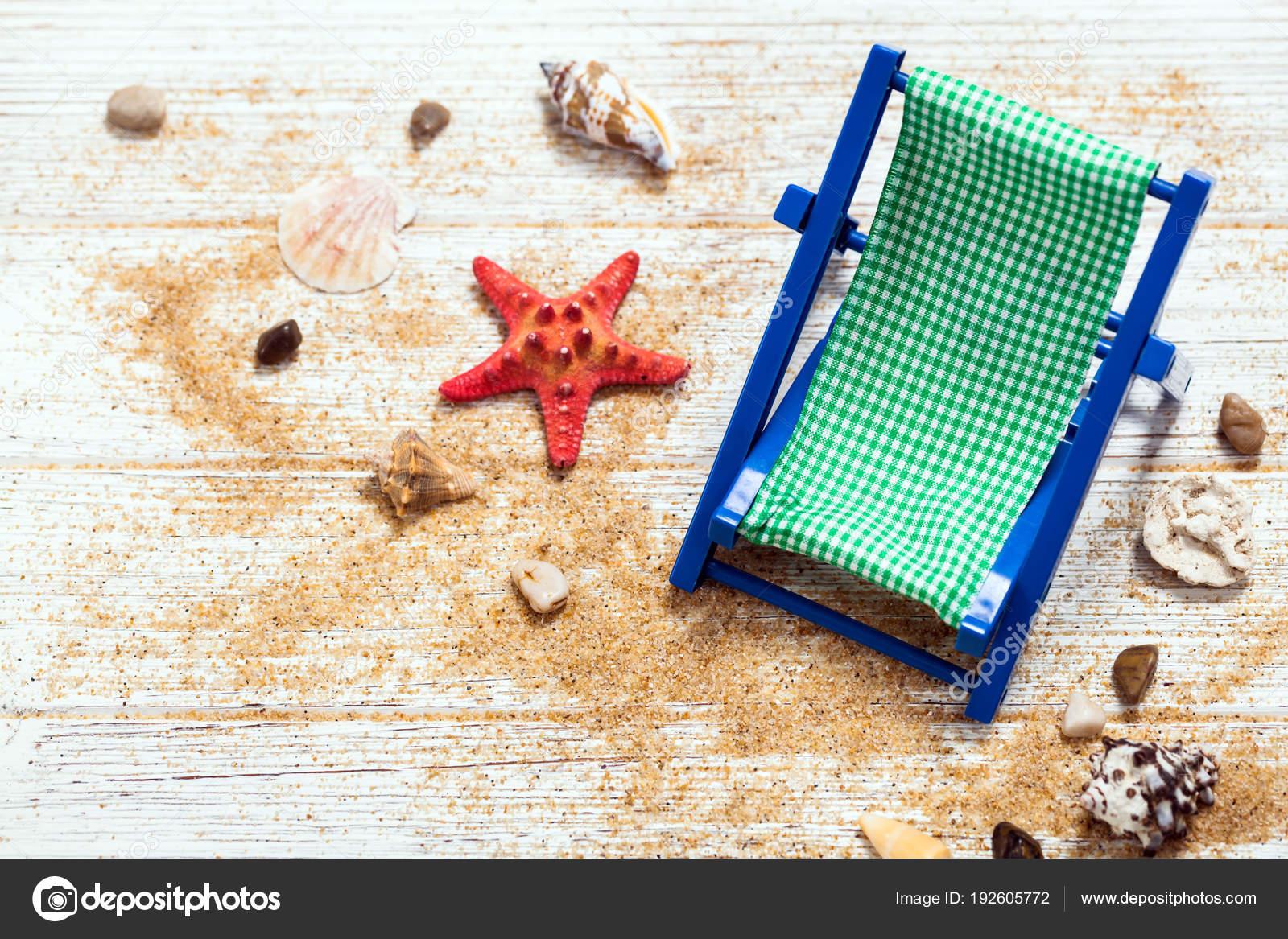 Sedia spiaggia conchiglie sabbia sulla lavagna legno sfondo
