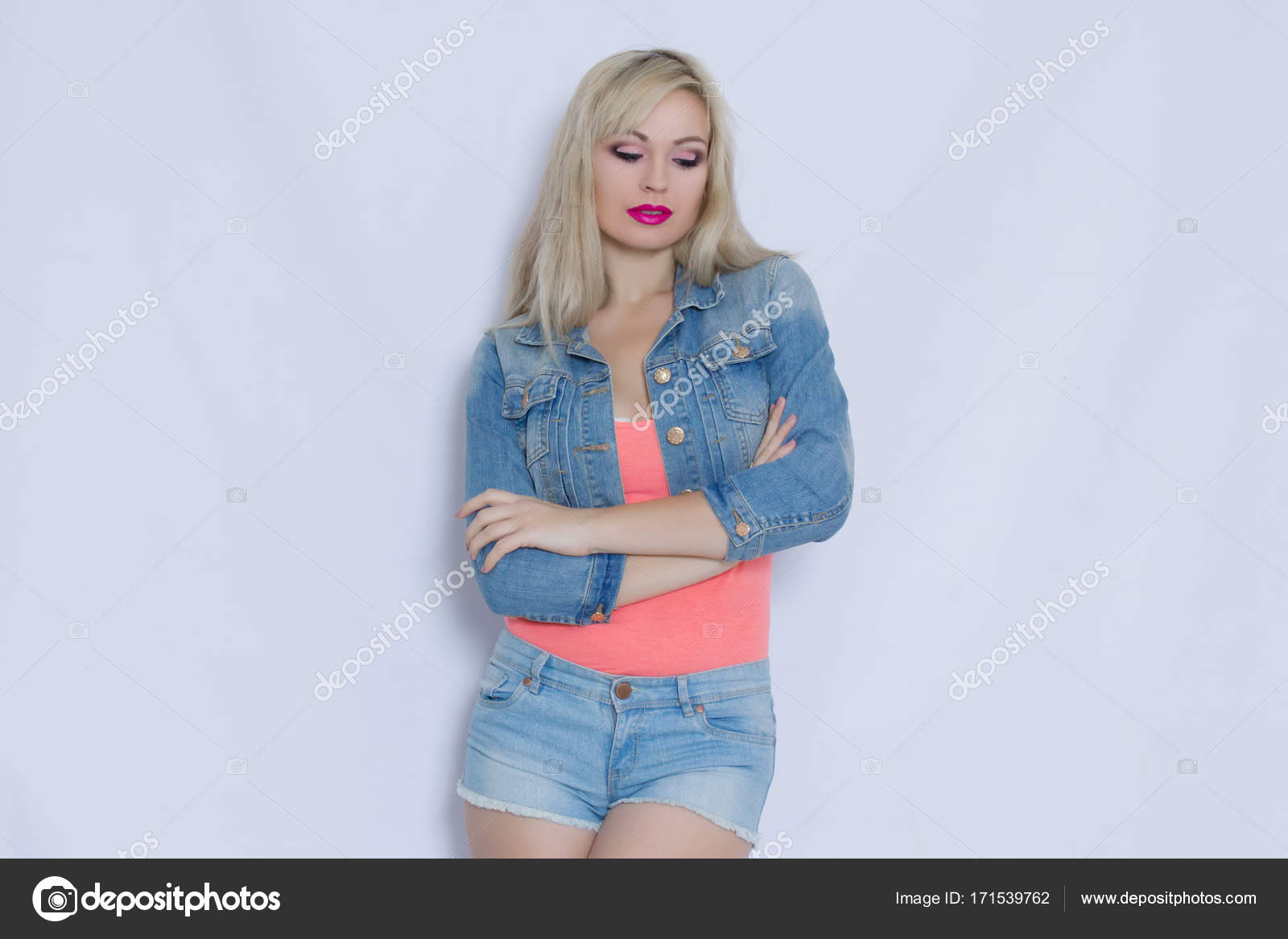 eb17f59efd2ee8 Beautiful blond young woman in pink tank top and jeans costume with shorts  and jacket posing and look to camera. Horizontal photos.