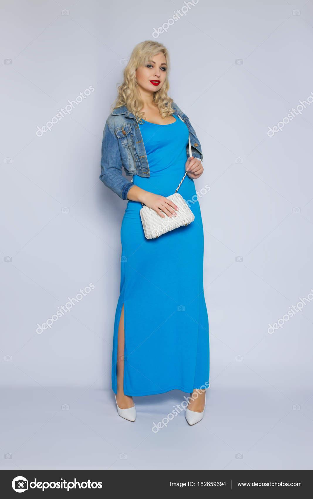e128018b3418 Ritratto dello studio di una bella giovane donna bionda con capelli ricci.  Una dolce ragazza è vestita in un vestito blu e una giacca di jeans