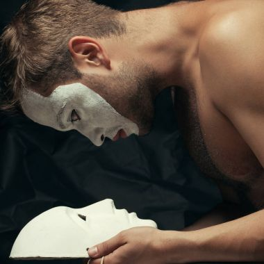 Mystery double concept. Arty portrait of circus performer holding white mask