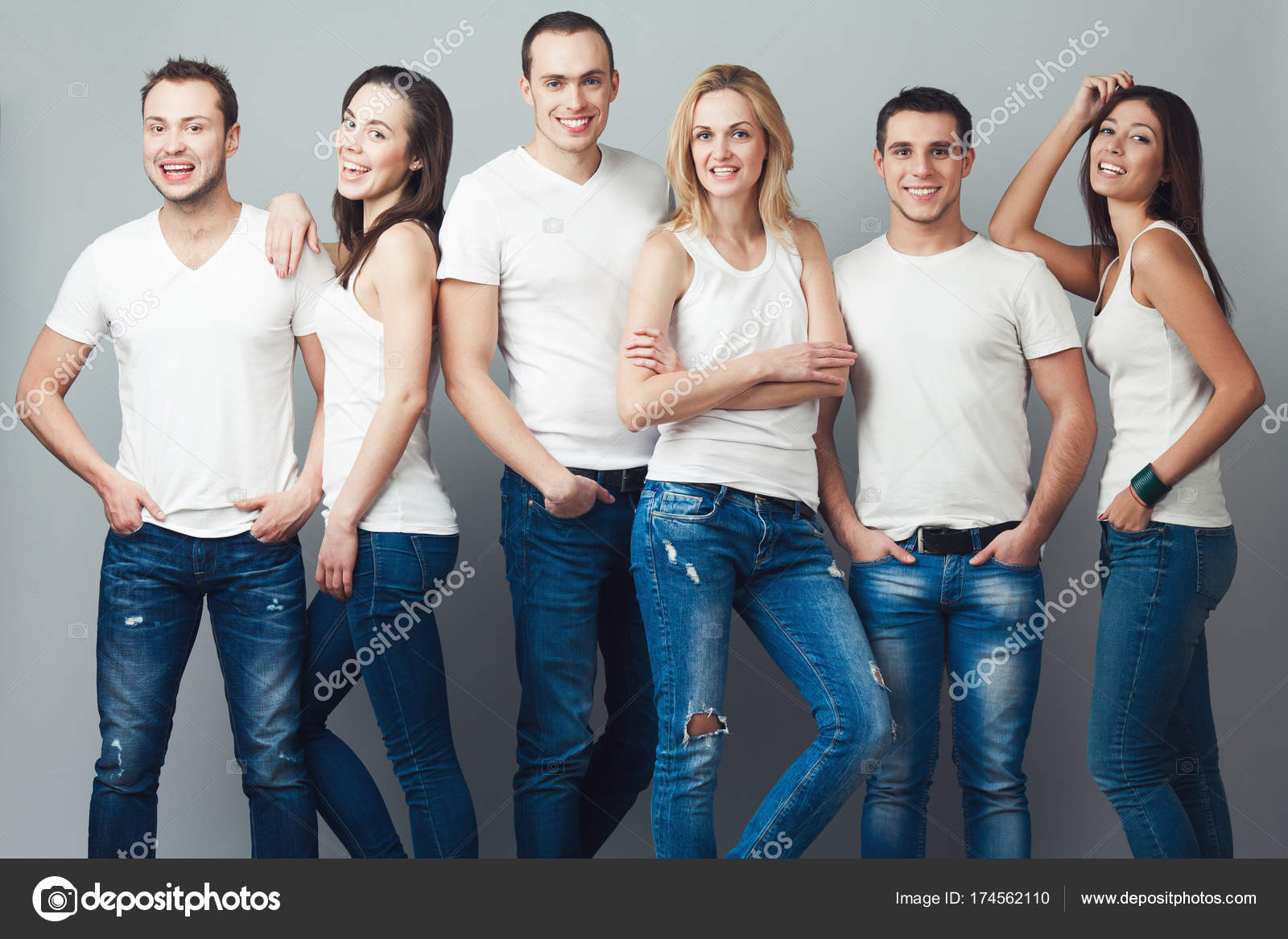 26abc3199b69 Ομάδα πορτρέτο του υγιή αγόρια και κορίτσια σε λευκό t-shirts, αμάνικο  πουκάμισα και τζιν μπλε μόνιμη και ποζάρουν πέρα από το γκρι φόντο. Αστικό  ύφος.