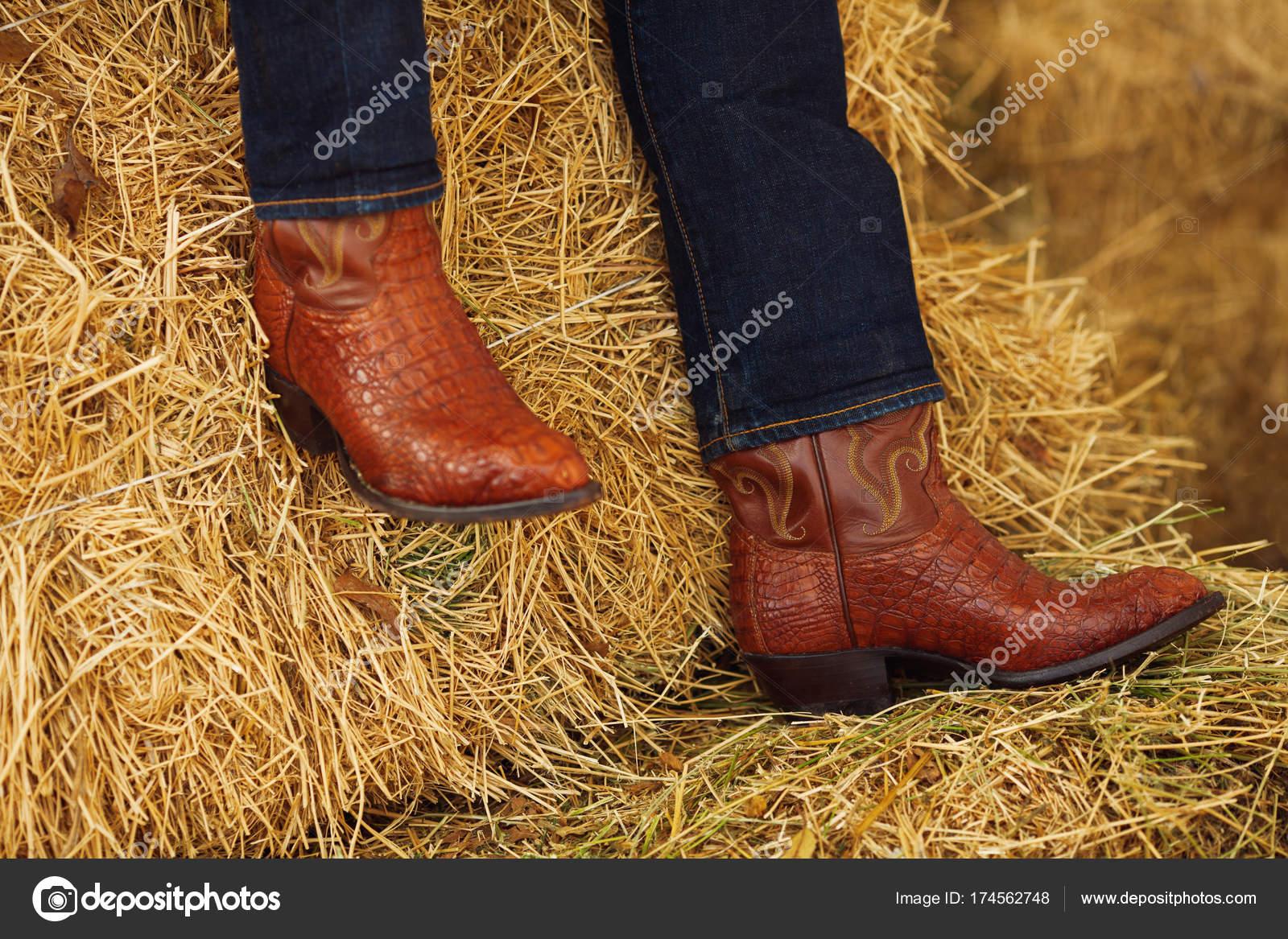 78123da89 Concepto de rodeo del oeste americano. Hombre en vaqueros y botas de cowboy  de cuero tradicional sentado en balas de heno. Estilo retro. De cerca.