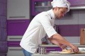 Tiramisu vaření koncept. Portrét zaměřený muž v uniformě kuchař