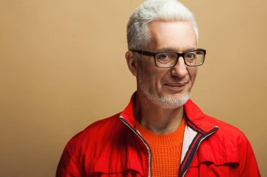 Fabulous at any age, eyewear concept. Portrait of fashionable 60-year-old man in red jacket over beige, pastel background. Trendy haircut, glossy grey hair. Close up. Copy-space. Studio shot