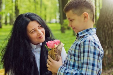 The son gives his mother a fresh bouquet of tulips flowers on a bench in the park.