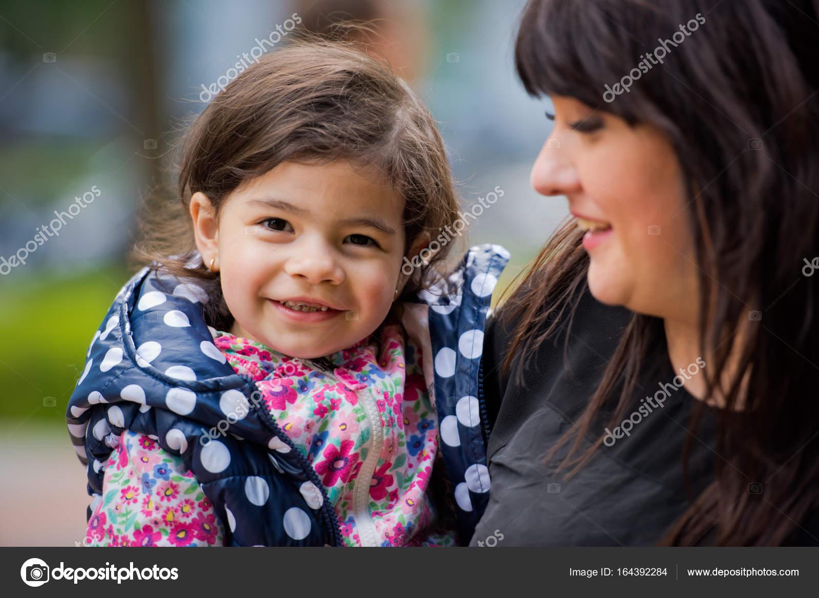 Una pequeña hija en brazos de su madre mira el marco y sonrisas. Día ...