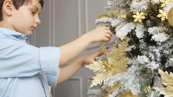 Porträt eines kleinen Jungen berührt ein Spielzeug am Weihnachtsbaum
