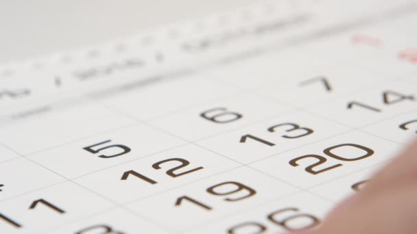 Signing a day on a calendar by red pen (square)