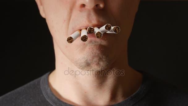 Wenige Zigaretten im Mund junger Erwachsener hängen herunter