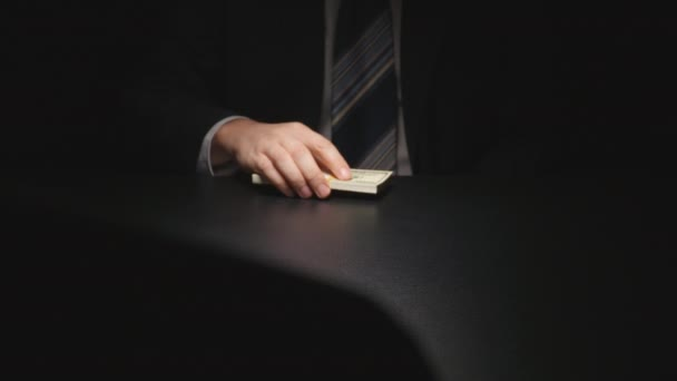Bribe: Businessman cautiously takes out from under table a money pack on a table - two person (US dollar)