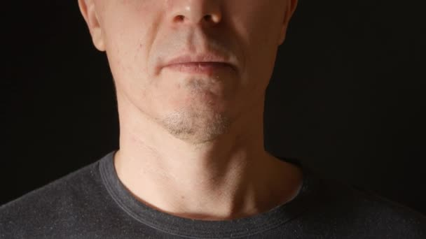 Gesicht eines jungen erwachsenen Mannes, der ein paar Zigaretten in den Mund nimmt