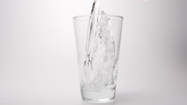 Slow Motion: Čistou vodu nalijte do průhledného skla na bílém pozadí