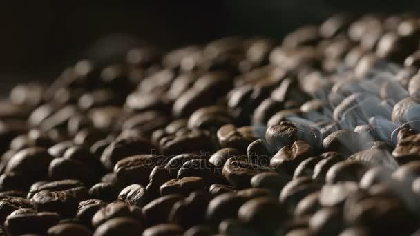 Nahaufnahme gerösteter Kaffeebohnen mit einem Rauch