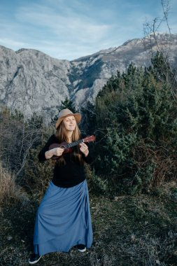 Young hipster woman in a hat playing on a ukulele on a mountain