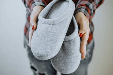 Female hands hold cozy slippers
