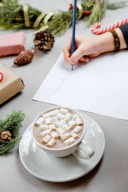 Cocoa with marshmallow and Boy writing letter to Santa Claus at