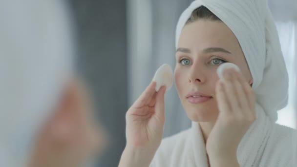 Krásná žena v bílém ručníku na hlavě a župan při pohledu v odrazu v zrcadle a čištění obličeje odstranění pleti make-up s bavlněným diskem, péče o pleť koncept.