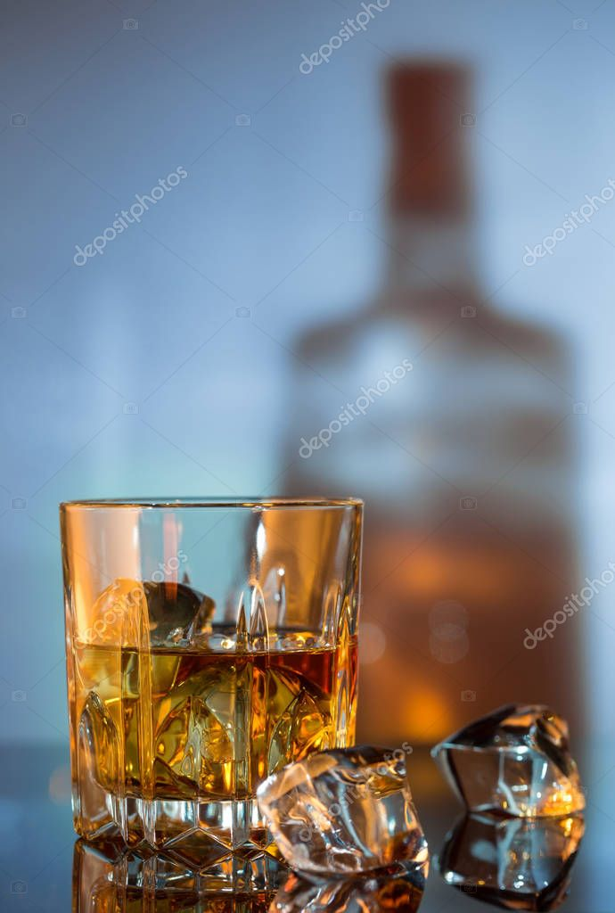 Glass of whiskey and ice against the background of bottle