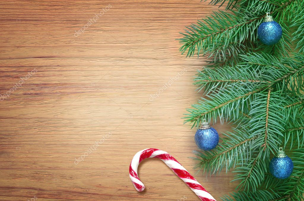 Fir tree branch with Christmas balls and candy on brown wooden background. Top view.