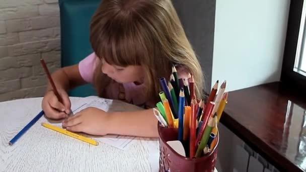Kislány ül az ablak mellett, és rajzol