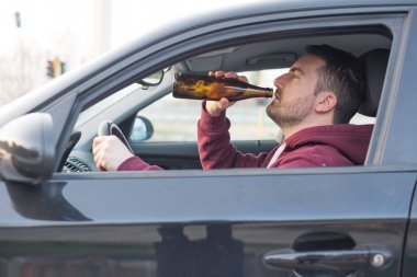 Drunk man driving his car and drinking