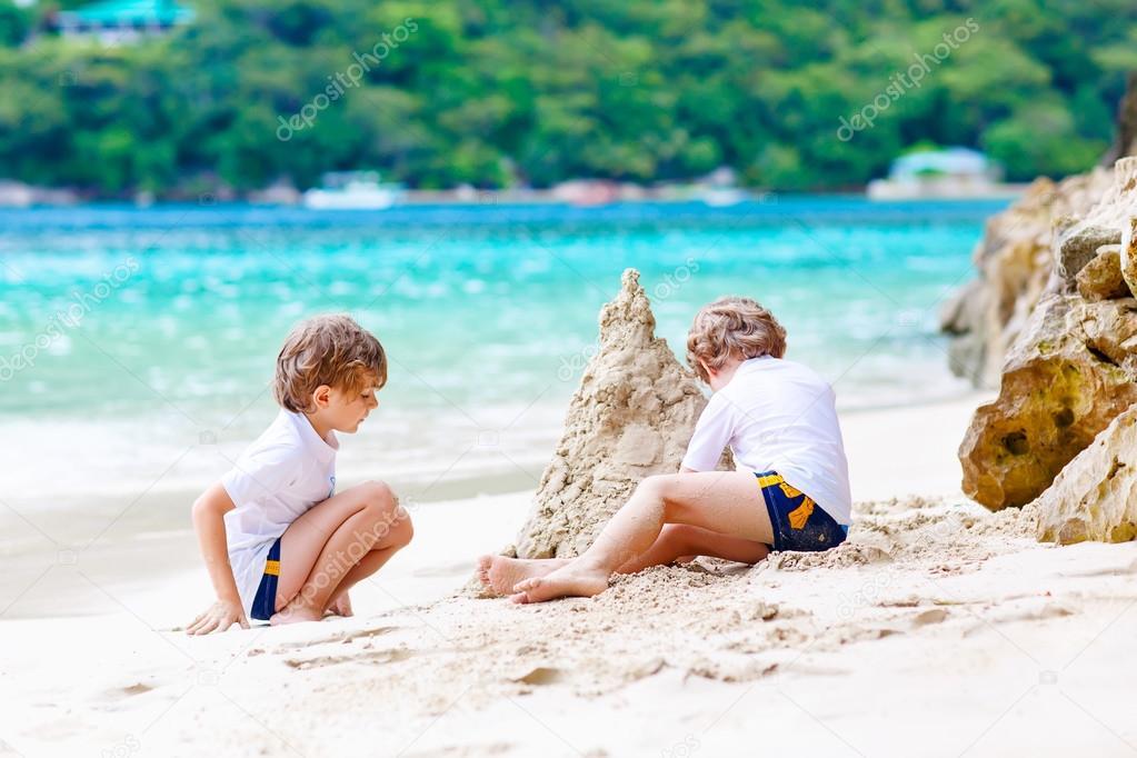 Due ragazzi di bambino costruendo castelli di sabbia for Disegni di casa sulla spiaggia tropicale