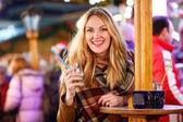Fotografie Frau trinkt heißen Punsch auf deutschem Weihnachtsmarkt.