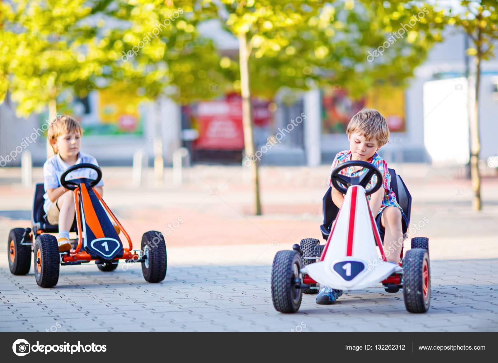 two little kid boys driving pedal race car in summer garden