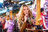 Frau trinkt heißen Punsch auf deutschem Weihnachtsmarkt.