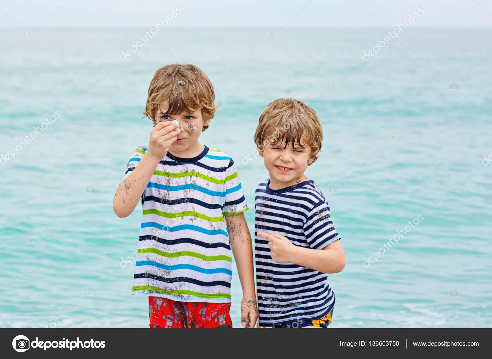 duas crianças brincando com areia na praia do oceano
