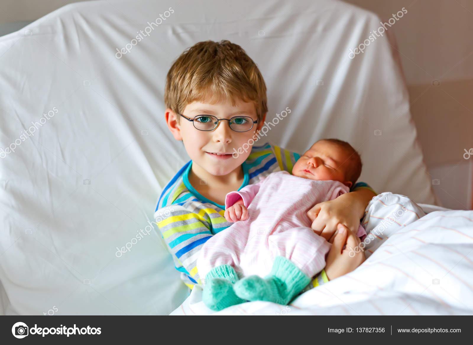 a58c2fc76ed3a Little kid boy holding his sleeping newborn baby sister in hospital ...