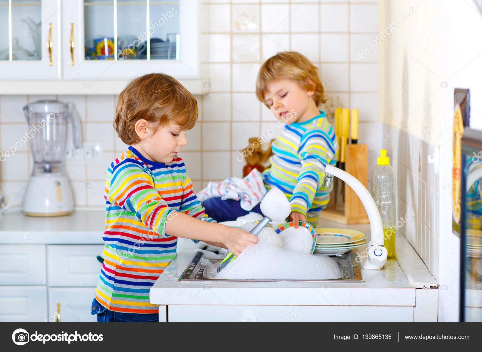 Dos Niños Poco Muchachos Lavando Platos En La Cocina