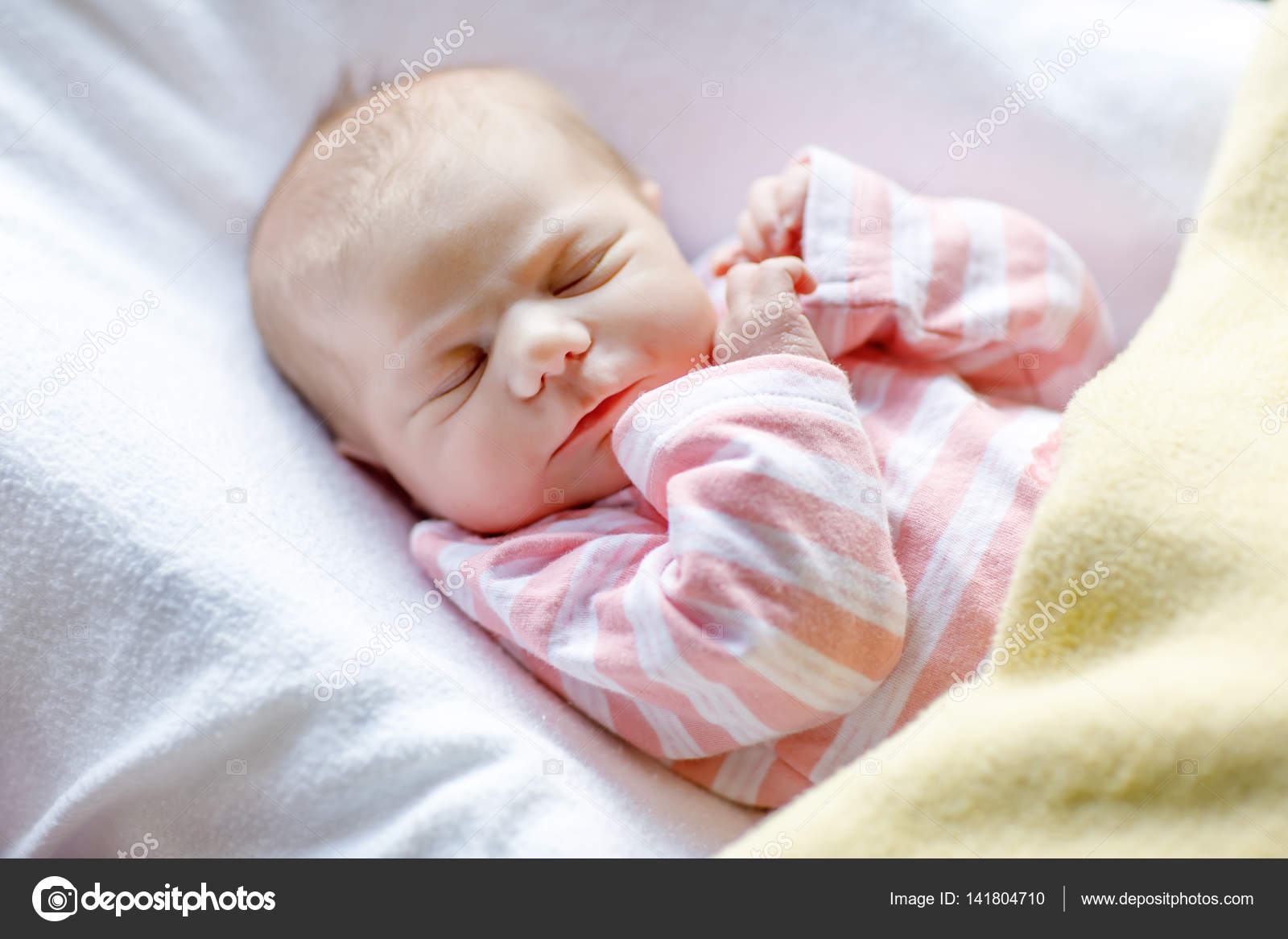 ecaa77ea1 Cute adorable newborn baby sleeping in white bed. New born child, little  girl laying in bed. Family, new life, childhood, beginning concept.