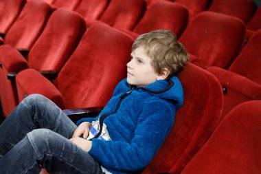 cute blond little kid boy eating popcorn at the cinema before the movie starts